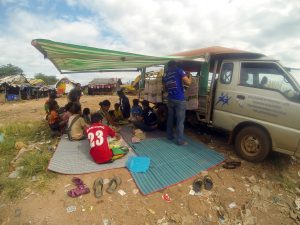 The bus awning creates shade and the matts are put out to create a mobile classroom