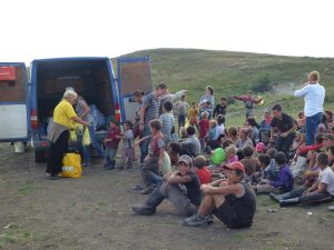 The volunteers handed out the yellow food packages to the children as they were called to the van. Over 150 children receive these packages twice a week.
