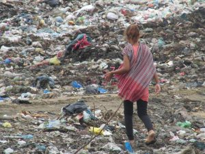 A young mother on the dump. There are around 100 people who work on this dump. Two thirds of which are children.